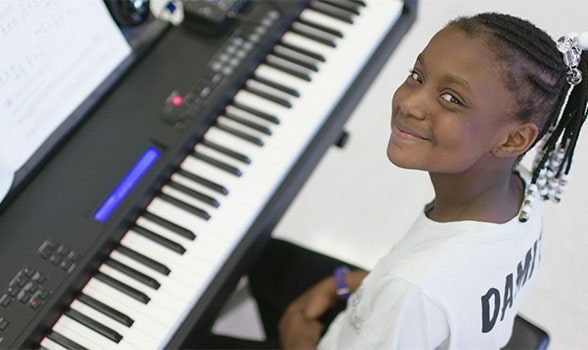 child smiling and sitting at keyboard