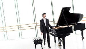 Elliot Wuu stands beside a piano for a portrait