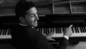emmet cohen smiles and turns while playing the piano