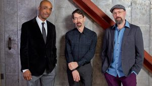 the Fred Hersch Trio poses for a portrait against a gray wall