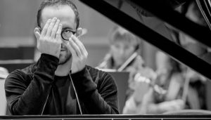 Igor levit sits behind a piano and covers one eye with his hand
