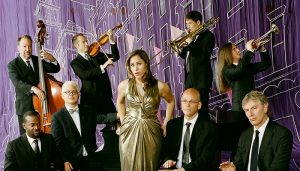 Members of pink martini pose for a portrait in front of a purple backdrop