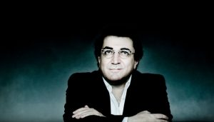 Sergei Babayan sits in front of a dark background with a blue light and looks up for a portrait