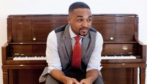 Sullivan Fortner sits in front of a piano