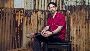 fred hersch poses for a portrait in front of an industrial wall