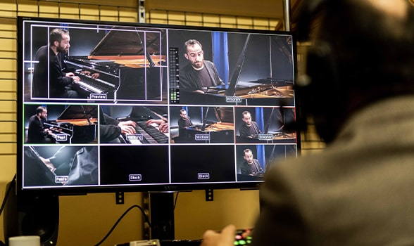 view from behind a technician watching igor levit perform on screen