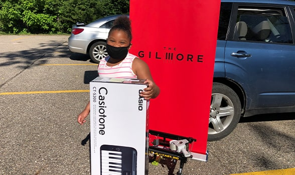 girl stands in front of the gilmore sign with a keyboard