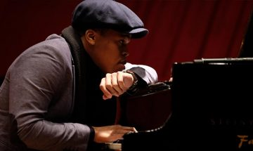 portrait of isaiah thompson resting at a piano