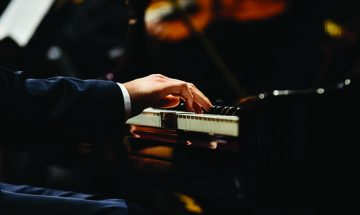 close up of man's hands playing piano