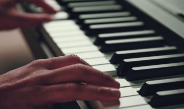 hands on white piano keys