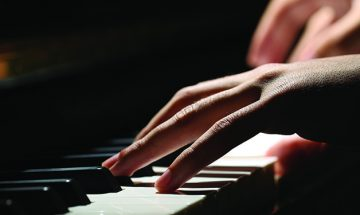 close up of hands on piano keys