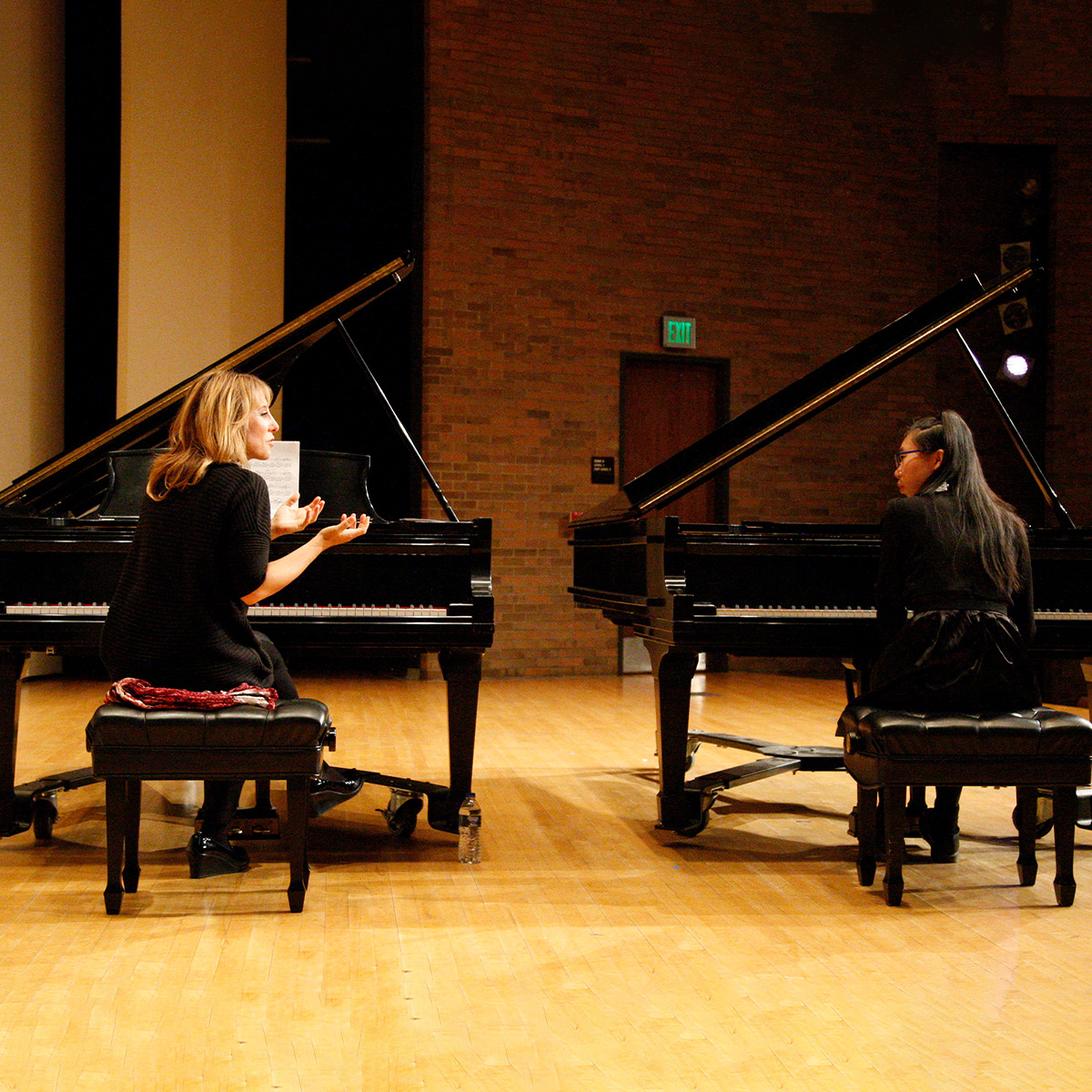 Two women talking while sitting at two separate pianos