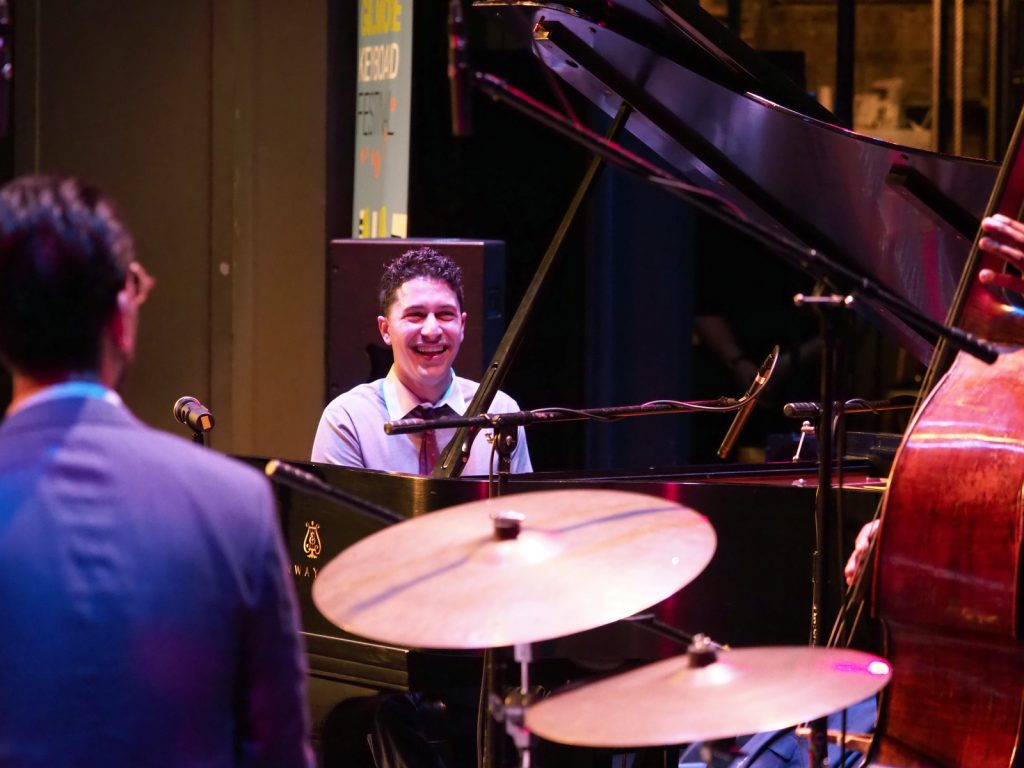 Emmet Cohen Trio pianist laughing on stage